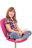 Little girl sitting on chair and play with tablet pc — Stock Photo