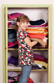 Little girl girl agrees clothes in a closet — Stok fotoğraf