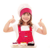 Happy little girl cook with thumbs up and cakes — Stock Photo