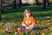 Happy little girl sitting in park — Stock Photo