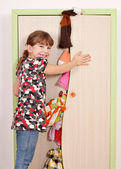 Little girl trying to close messy closet — Стоковое фото