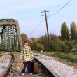 Little girl with suitcase and teddy bear standing on railroad — Stock Photo