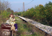 Little girl sitting on suitcase and waiting for train — Stock Photo