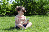 Happy little girl sitting on grass and play with tablet — Stock Photo
