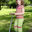 Little girl with scooter in park — Stock Photo