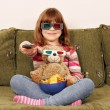 Stock Photo: Little girl and teddy bear with 3d glasses watching tv