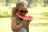 Little girl with sunglasses eat watermelon — Stock Photo