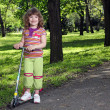 Beautiful little girl with scooter in park — Stock Photo