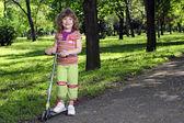 与踏板车在公园里的漂亮的小女孩 — 图库照片