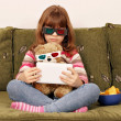 Stock Photo: Little girl and teddy bear with 3d glasses watching movie on tab