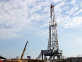 Oil drilling rig and crane on field — Stock Photo
