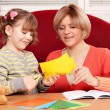 Stock Photo: Happy mother and daughter cutting paper