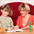 Happy mother and daughter doing homework — Stock Photo