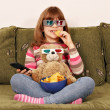 Stock Photo: Little girl with 3d glasses eat chips and watching tv
