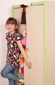 Happy little girl trying to close messy closet  — Stock Photo