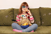 Little girl with 3d glasses eat chips and watching tv — Stock Photo