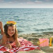 Happy little girl lying on beach summer season — Stock Photo