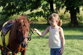 Beautiful little girl and pony horse pet on field — Stock Photo