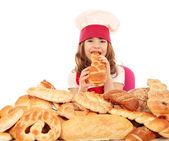 Hungry little girl cook eat bread — Stock Photo