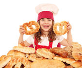 Happy little girl cook hold pretzels — Stock Photo