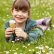 Happy little girl lying on grass and eat ice cream — Stock Photo #43881611