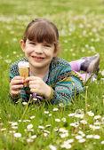 happy little girl lying on grass and eat ice cream — Foto de Stock