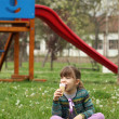 Little girl sitting on grass and eat ice cream — Stock Photo #44183909