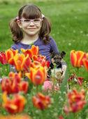 Little girl with puppy in the tulip flower garden — ストック写真