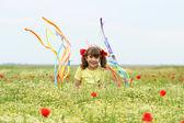 Heureuse petite fille agitant avec des rubans colorés sur mea wildflower — Photo