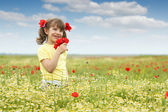 Beautiful little girl with poppy flowers on meadow — Stock Photo