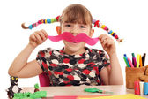 Happy little girl makes paper mustache — Stockfoto