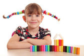 Beautiful little girl with plasticine — Stock Photo