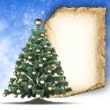 Christmas tree and blank paper sheet on blue background — Stock Photo