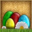 Colored Easter eggs and spring flowers on patterned background — Stock Photo