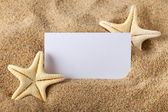 Starfish and blank paper sheet on beach — Stock Photo