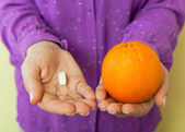 Woman hand with pills medicine tablets and orange — Stock Photo