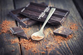 Closeup of dark choclate and cocoa Powder over spoon — Stock Photo