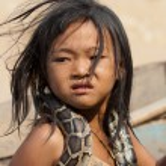 Little asian girl holding snake on her shoulders. — Stock Photo