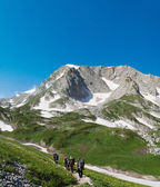Group of tourists walking along the trail in the mountains of Ad — Stock Photo