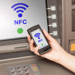 Withdrawing money atm with mobile phone a NFC terminal - Stock Photo