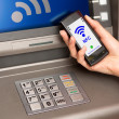 Stock Photo: Withdrawing money atm with mobile phone a NFC terminal