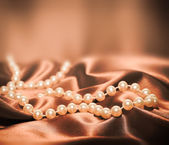 Pearls on a silk fabric background — Stock Photo