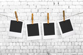 Photos hanging on a clothesline on brick wall background — Stock Photo