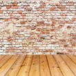 Old brick wall on wood floor — Stock Photo #35175381