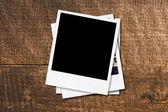 Blank photo frames on old wooden background. — Stock fotografie