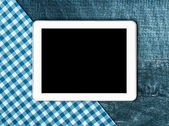 Tablet, tablecloth textile on wooden table — Stock Photo