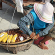 The seller on a beach, PATTAYA, THAILAND - december 16: Thai woman sells  fruits to tourists on   Samet beach. December 16 2012 in Pattaya. — Stock Photo