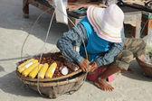 The seller on a beach, PATTAYA, THAILAND - december 16: Thai woman sells fruits to tourists on Samet beach. December 16 2012 in Pattaya. — Stock Photo