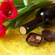 Royalty-Free Stock Photo: A bottle of wine, chocolates and three red tulips
