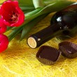 A bottle of wine, chocolates and three red tulips — Stock Photo